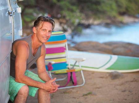 easygoing: Male European surfer sitting in van door on beach Stock Photo