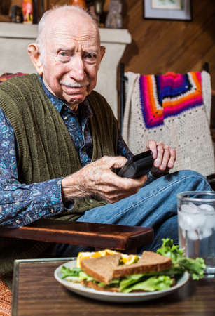 disapproving: Older gentleman looking unhappily at a sandwich