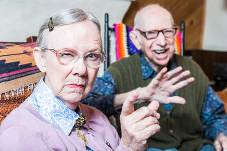 male senior adult: Angry old couple sitting in living room woman pointing