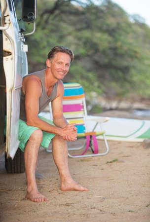adult male: Adult male surfer sitting in van door on beach