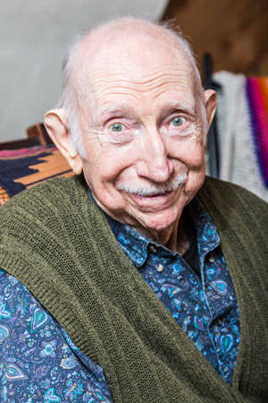 elderly adults: Elder man smiling at camera seated in his livingroom