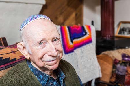 observant: Elderly gentleman in green vest and yarmulke seated in his livingroom