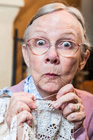 knit: Elder woman with crochet and funny facial expression
