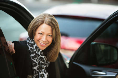 open car door: Beautiful smiling adult business woman in car with open door