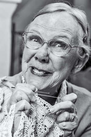 odd: Silly old lady with crochet and odd expression