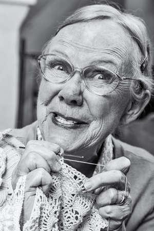 señora mayor: Tonto anciana con crochet y extraña expresión
