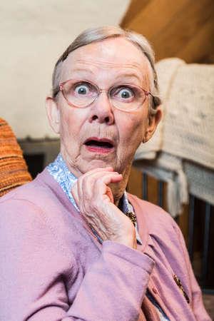 Verbaasd oude matrone vrouw kijkt naar de camera