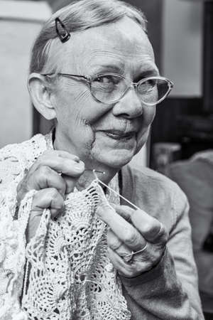 demure: Elderly woman in sweater crocheting with demure smile