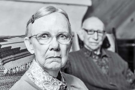 scowling: Elderly scowling couple seated in indoors woman
