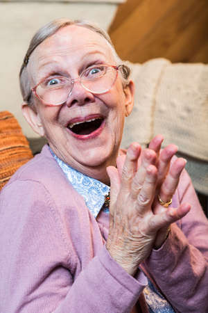 grandma: Joyful old woman in pink sweater with hands together