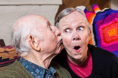 cheek: Elderly gentleman kissing elderly woman on cheek in livingroom