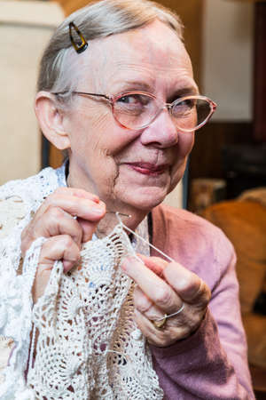 demure: Elderly woman in pink sweater crocheting with demure smile
