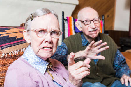Angry old man and woman scowling at camera sitting in livingroom