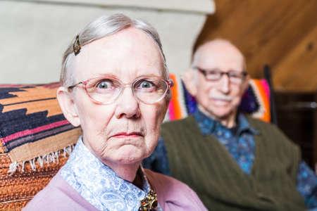 Oude paar zitten in de woonkamer vrouw het voorhoofd fronsen