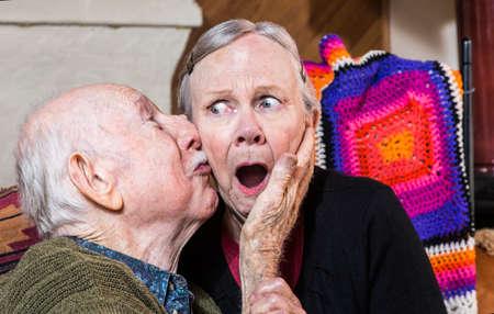 lustful: Older gentleman kissing older shocked woman on cheek in livingroom