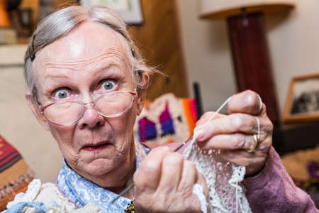 Elderly woman crocheting while looking at camera