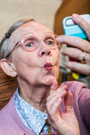 Glückliche ältere Frau, die Ente Gesicht selfie
