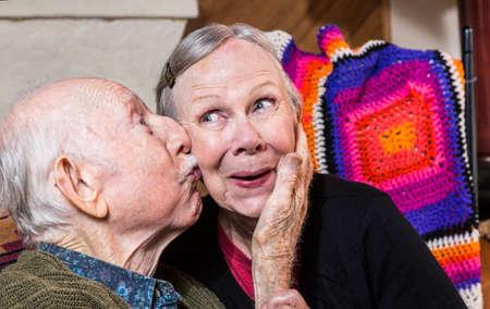 Bejaarde man vrouw zoenen op de wang in binnenshuis Stockfoto