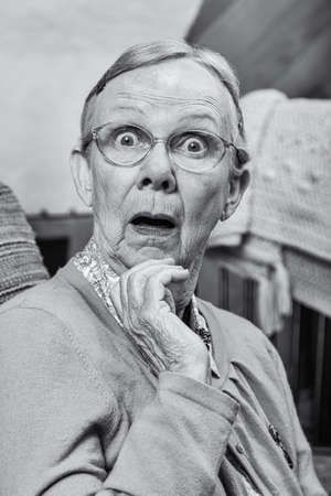 matron: Surprised senior matron woman looking at camera