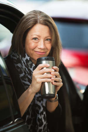 thermos: Cheerful mature adult woman holding coffee thermos