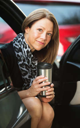 beautiful middle aged woman: Female executive sitting in door of car