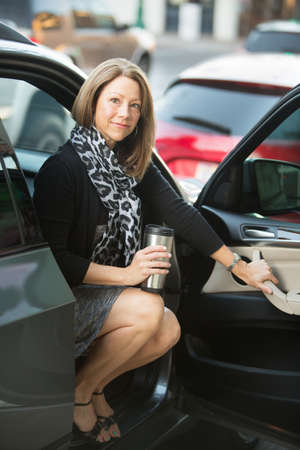 executive woman: Happy executive woman with scarf sitting in open car