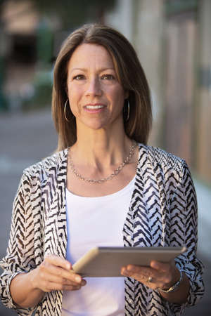 confident woman: Beautiful confident business woman holding a tablet computer Stock Photo