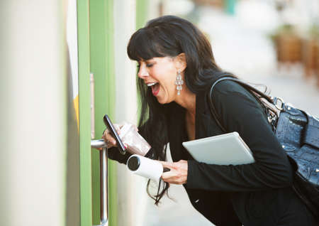 open business: Attractive woman with her hands full attempting to open a door