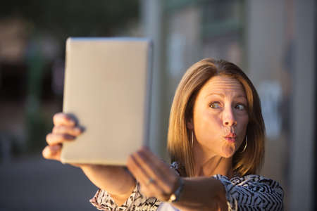 puckering lips: Woman posing for picture for tablet computer self-portrait Stock Photo