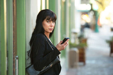 black professional: A beautiful woman holding cellphone on a downtown street