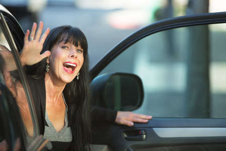 exits: Attractive woman waving as she exits vehicle on downtown street