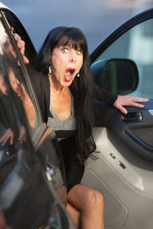 mature women: A woman exits a vehicle with look of surprise on downtown street Stock Photo