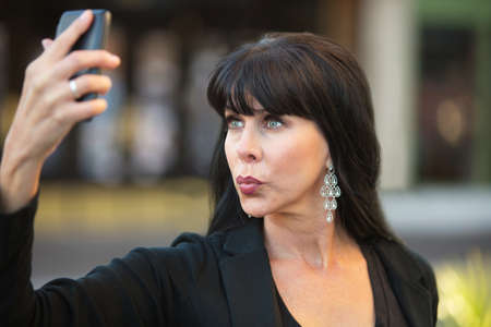smooching: Attractive woman taking selfie with black cell phone