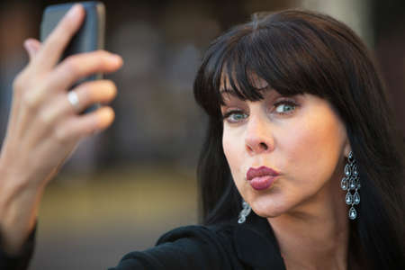 smooching: Attractive woman taking silly selfie with black cell phone