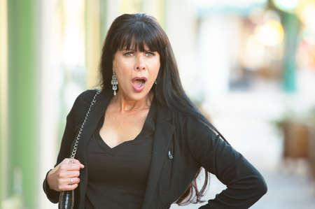 mature women: Beautiful woman on a downtown street looking shocked