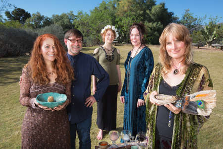 practitioners: Five smiling Wicca practitioners standing outdoors with smudge stick Stock Photo