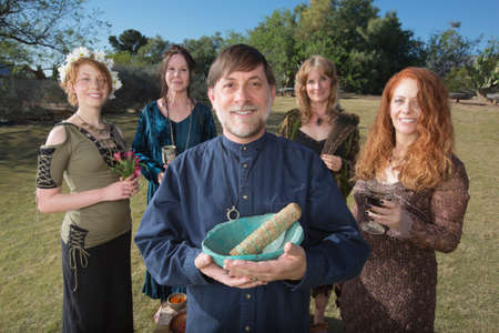 smudge: Modern Wicca priest holding sage smudge stick outdoors