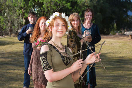 Young pagan woman with group holding a stick pentagram