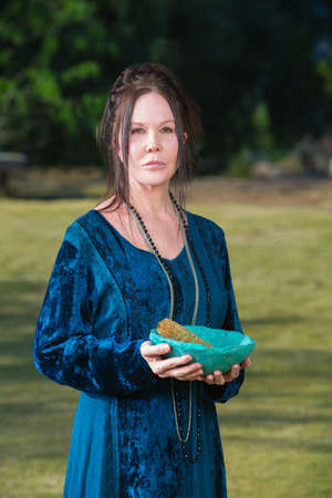 priestess: Serious Wicca priestess with blue bowl sage incense