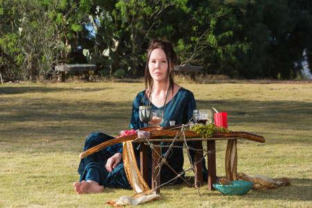 pagan: Serious priestess in outdoor pagan altar ceremony