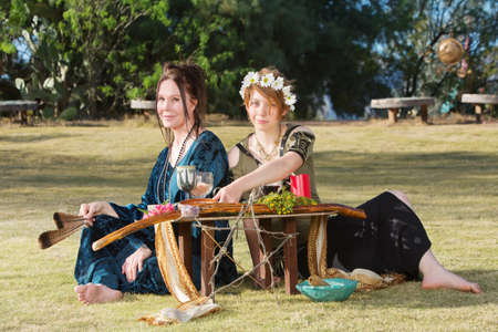wicca: Pair of beautiful pagan women at outdoor altar