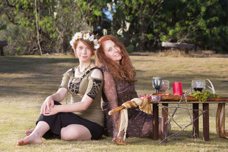 wicca: Two smiling pagan women at outdoor altar with pentagram