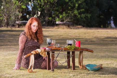 Beautiful priestess in outdoor pagan ritual with altar