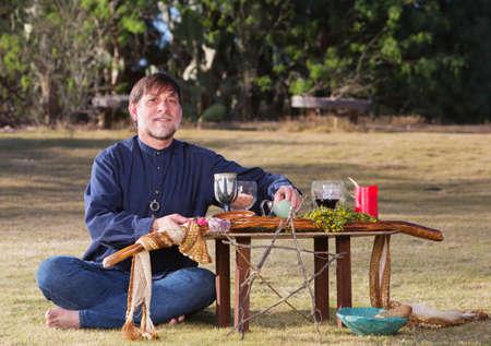 priestess: Single bare foot male at pagan altar outdoors