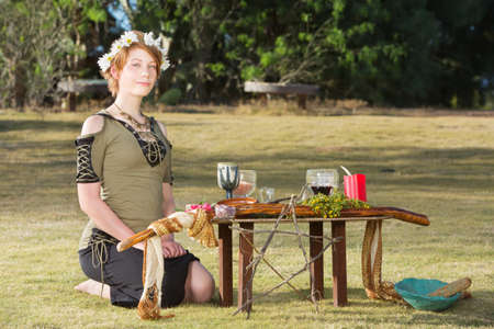 Cute pagan woman with wreath sitting at outdoor altar