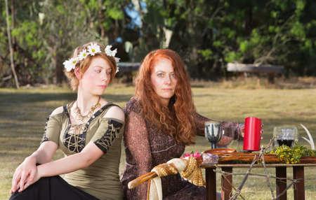 pagan: Two serious pagan females sitting at altar with candles Stock Photo