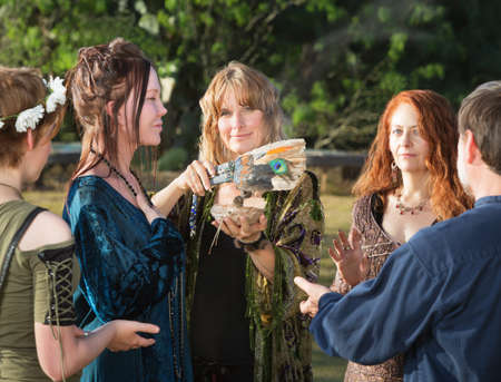 wicca: Group of Wicca men and women using feather and incense Stock Photo