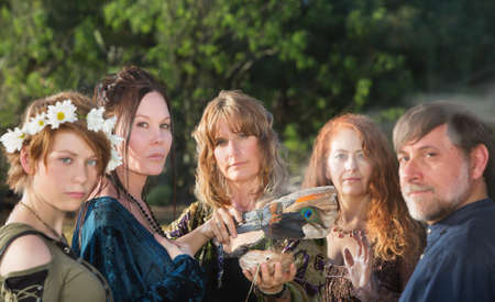 pagan: Five witches with feather and sage incense outdoors