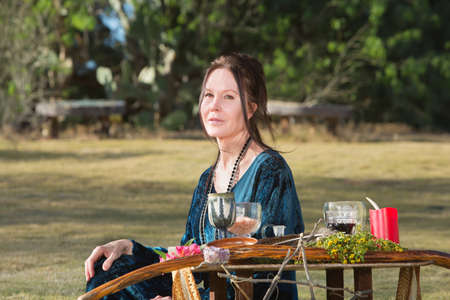pagan: Pagan woman adult with altar sitting outdoors Stock Photo