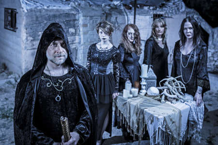 Group of five scary witches outdoors at a sacrifice table